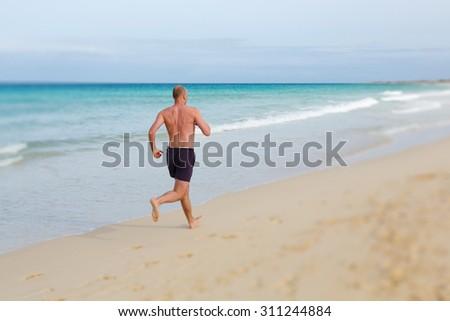 Man running on beach - stock photo