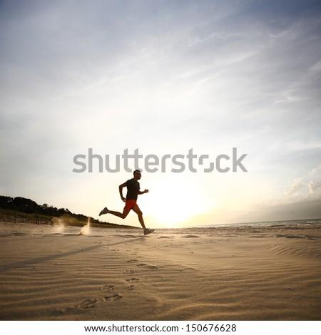 Man running on beach at sunset - stock photo