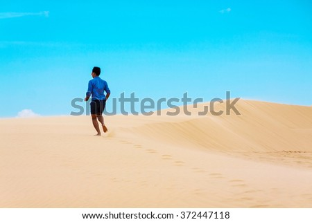 Man running on beautiful inspirational desert dunes on sunny summer day. - stock photo