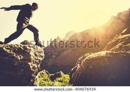 Man running on Mountains jumping cliff over lake Skyrunning sport Lifestyle Travel concept outdoor  - stock photo
