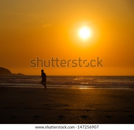 Man running on the beach at sunset