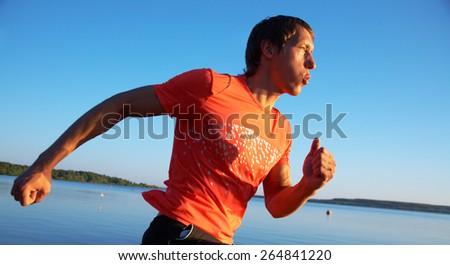 Man running on the beach at sunset - stock photo