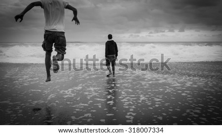 man running on the beach to the sea, black and white.