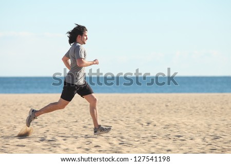 Man running on the beach with the sea in the background - stock photo