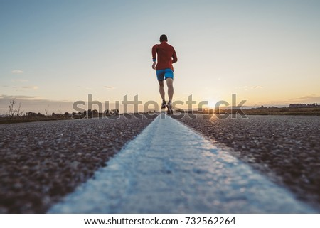 Man running on the line on a paved road at the sunrise