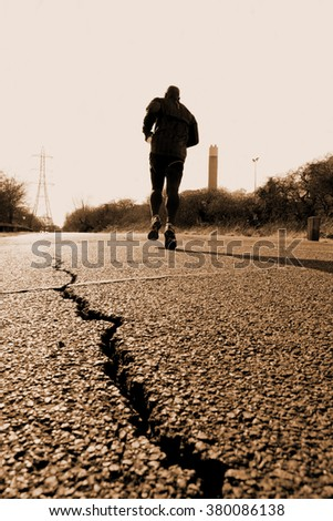 Man running on the road with cracked asphalt - stock photo