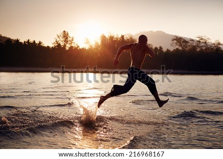 Man running on the sea at sunrise