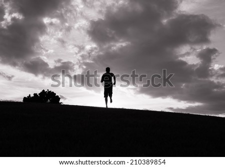 Man running outdoors during the sunset. - stock photo