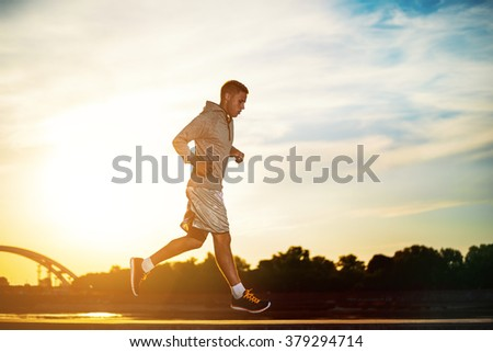 Man running outdoors on a sunny day.Young male jogger athlete training and doing workout outdoors in city. - stock photo