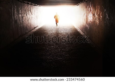 Man running through the tunnel in the sun - stock photo