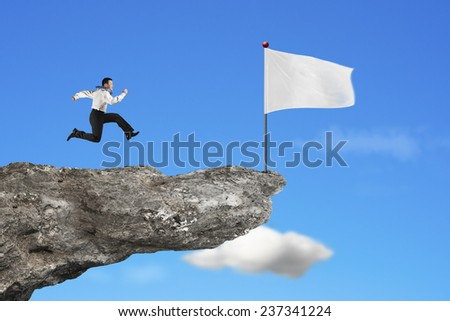man running to blank white flag on cliff with natural sky cloud background - stock photo