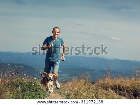 Man running with his dog on the mountain tableland - stock photo