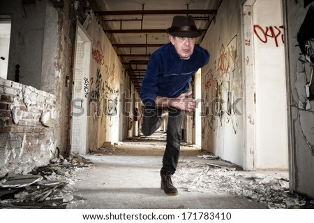 Man runs away in abandoned building - stock photo