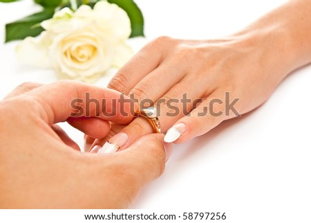 Man's and woman's hands with golden ring. White background