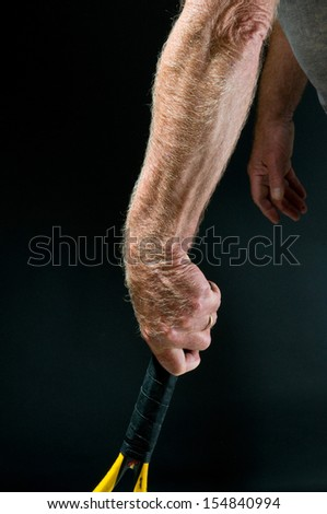 Man's arm and tennis racket - study of athlete's forearm highlighting muscles and arm hair - stock photo