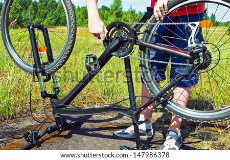 Man's arms fixing a bike in a grassy field. Horizontally framed photograph - stock photo