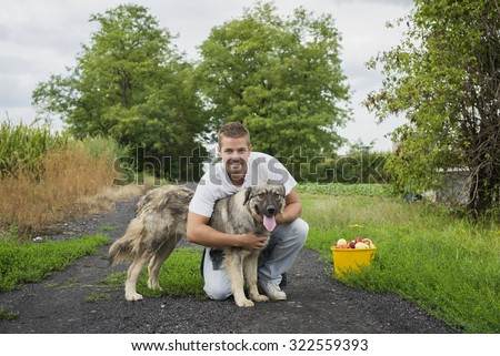 Man's best friend. Young man hugging a dog, both looking at camera. Bucket with fruit stands next to them.