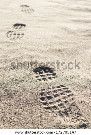Man's boots footmarks on the sand.