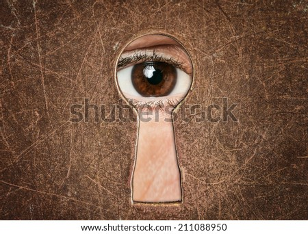 Man's eye looking through a keyhole antique door closeup  - stock photo