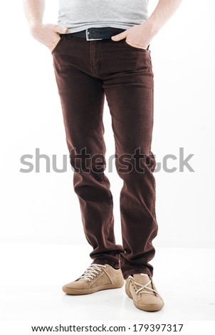 Man's feet in trousers and brown shoes close up, isolation on white