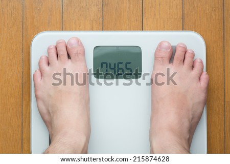 Man's feet on weighting scale - stock photo
