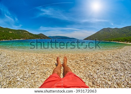 Man's feet relaxing in a Beatiful Bay with Clear blue water