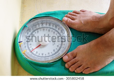 Man's feet standing on weighing machine, weighing scale - stock photo