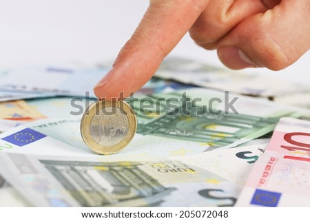 Man's finger holding one euro coin on euro banknotes - stock photo