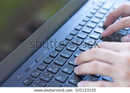 Man's fingers typing on a keyboard - stock photo