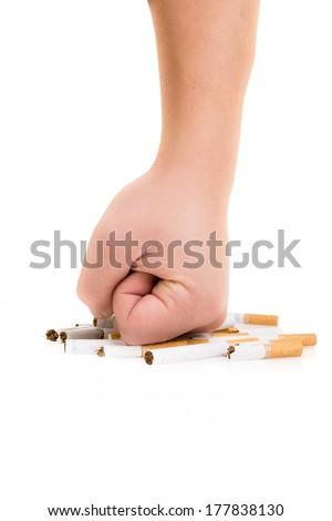 Man's fist crushing cigarettes isolated on white background - stock photo