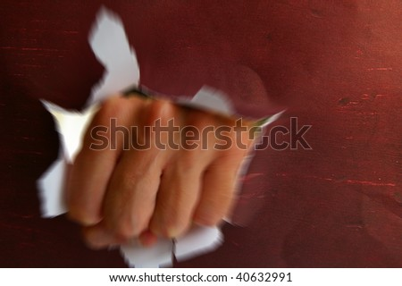man's fist violently punching thru a hole - stock photo