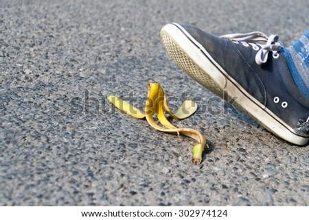 man's foot above banana peel laid on road - stock photo
