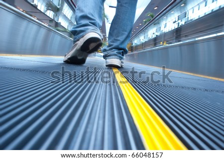 Man's foot walking in airport escalator perspective view (ground level) - stock photo