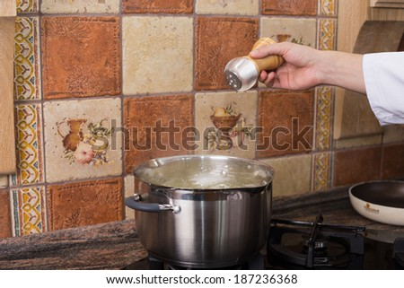Man's hand adding salt into the hot water in the kitchen - stock photo