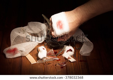 Man's hand chopped broken glass on the background of dark wood - stock photo