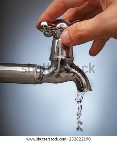 man's hand closes the leakage of water from the faucet Metal - stock photo