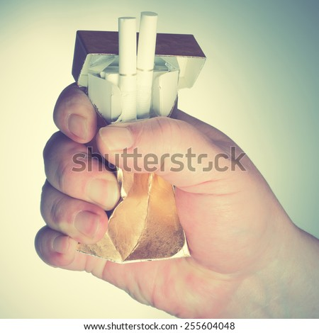 Man's hand crushing cigarette box. Retro style filtred image - stock photo