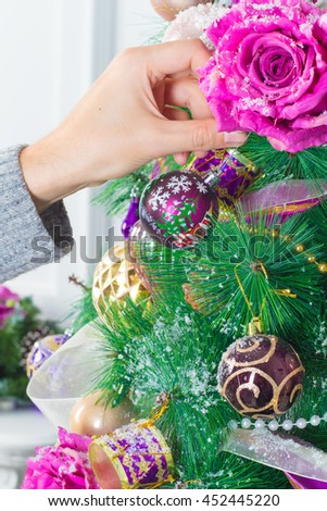 Man's hand decorating christmas tree with colorful christmas bauble - stock photo