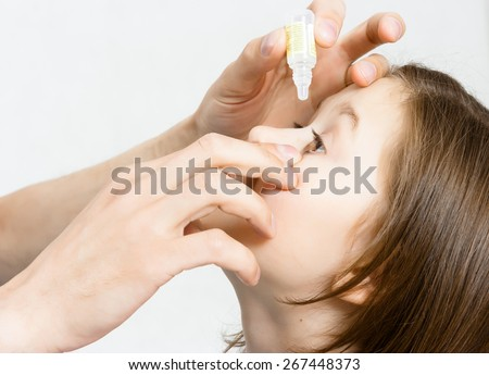 Man's hand dripping drug solution in the eyes of a child