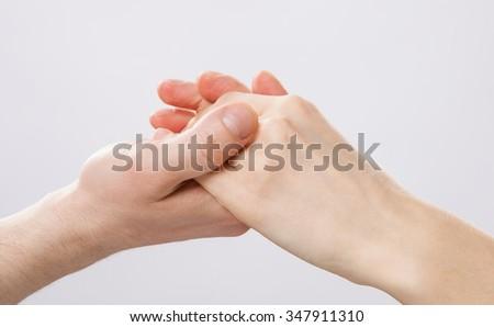 Man's hand gently holding woman's hand - closeup shot - stock photo