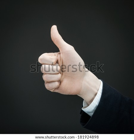 Man's hand giving a thumbs up on a black background. - stock photo