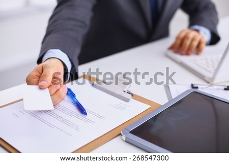 Man's hand giving business card  - stock photo
