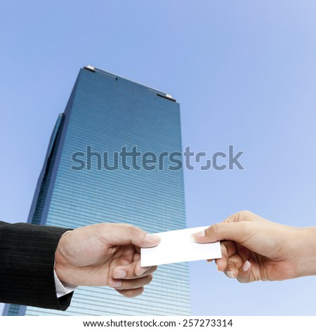 Man's hand giving business card - closeup shot on blur office buliding background - stock photo