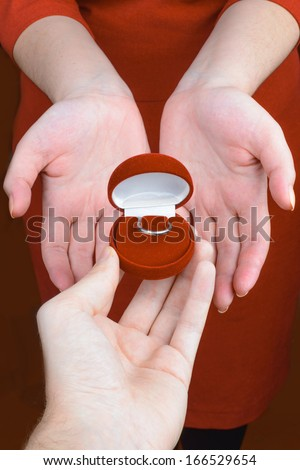 Man's hand giving to her red jewelry box with ring  - stock photo