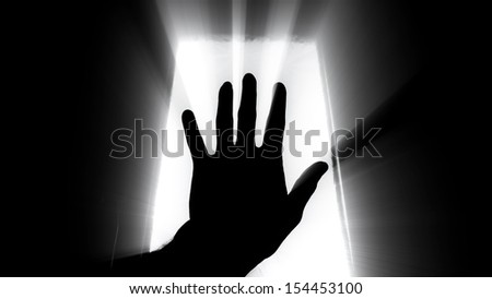 Man's hand held up to the sky with window light and rays of sunshine streaming between the fingers.