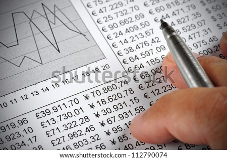 Man's hand holding a pen on top of a document with numbers and a chart - stock photo