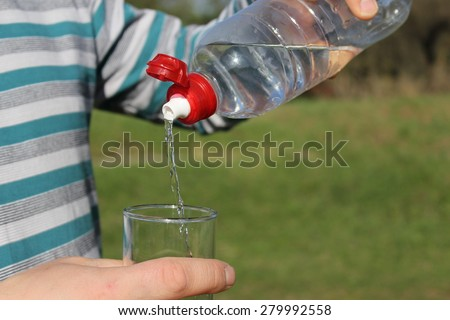 Man's hand holding a plastic bottle and pours water into a glass. Bottle and glass in focus. The background is the green grass. The water flows in a thin stream into a glass.