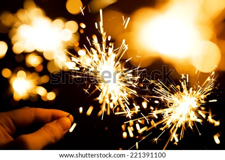 man's hand holding a sparkler - stock photo