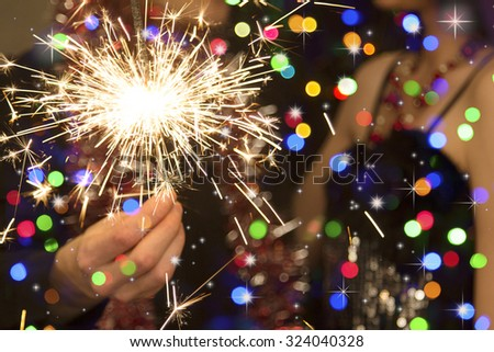 man's hand holding a sparkler during christmas - stock photo