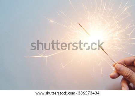 man's hand holding a sparkler on the white background - stock photo